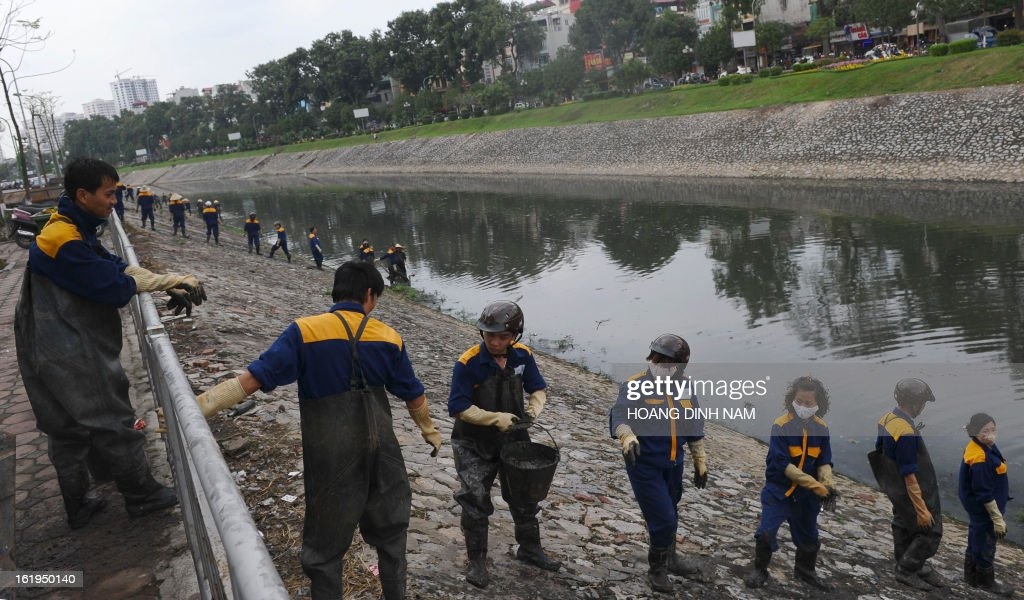 Hanoi's municipal environmental workers clear mud and garbage from a portion of the very polluted canal of To Lich on February 18, 2013. AFP PHOTO/HOANG DINH Nam