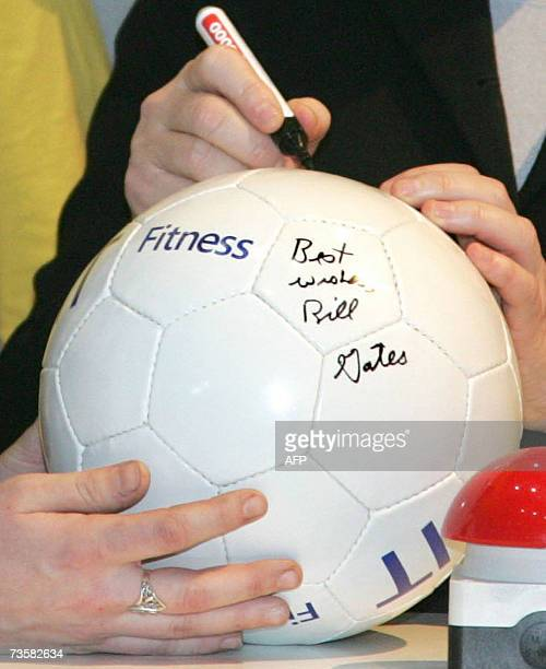German Chancellor Angela Merkel signs a football on which Microsoft chief Bill Gates has signed before at the Microsoft stand at the CeBIT computer...