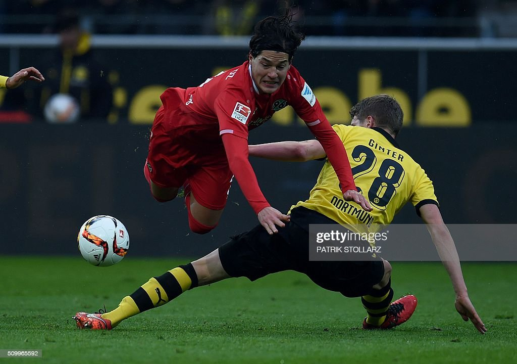 Hanover's Chilean defender Miiko Albornoz and Dortmund's defender Matthias Ginter vie for the ball during the German first division Bundesliga football match of Borussia Dortmund vs Hannover 96 in Dortmund, western Germany, on February 13, 2016. / AFP / PATRIK STOLLARZ /