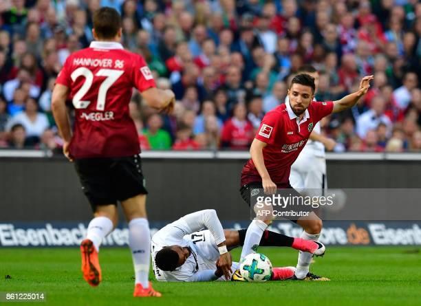 Hanover's German midfielder Pirmin Schwegler and Hanover's German defender Julian Korb vie for the ball with Frankfurt's Ghanaian midfielder...