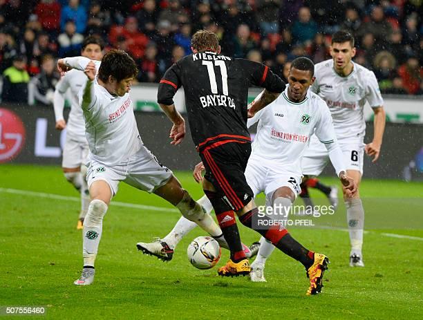 Hanover's Japanese defender Hiroki Sakai and Hanover's Brazilian defender Marcelo stop Leverkusen's forward Stefan Kiessling during the German first...