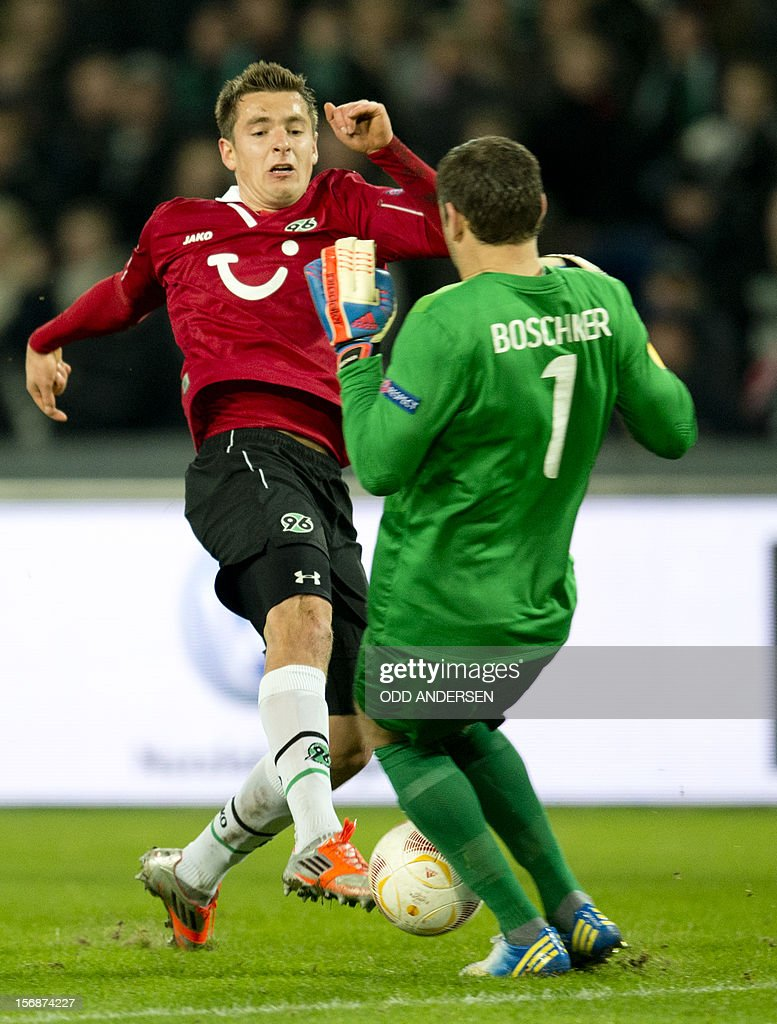 Hanover's Polish striker Artur Sobiech (L) has his shot blocked by Twente's goalkeeper Sander Boschker during the UEFA Europa League group L football match between Hannover 96 and Twente in Hanover on November 22, 2012. The match ended in 0-0 draw.