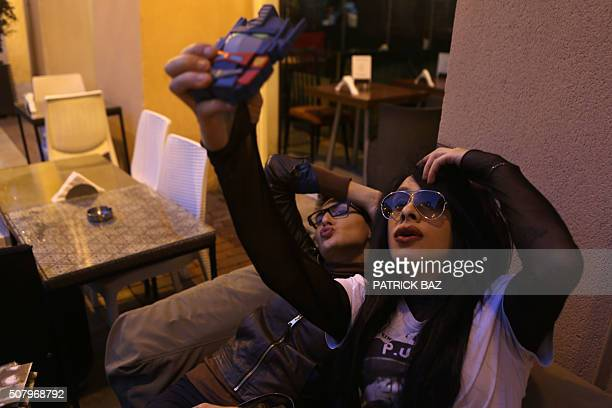 Hans a 22yearold Lebanese drag queen takes a selfie with her transgender friend Toy at a cafe in downtown Beirut on February 1 2016 Hans works as a...