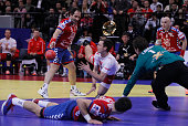 Hans Lindberg of Denmark jumps to save a ball with Alem Toskic of Serbia during the Men's European Handball Championship 2012 final match between...
