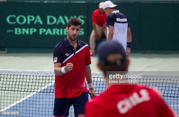 Hans Podlipnik of Chile celebrates a point with teammate Nicolas Jarry during the Davis Cup first round double tennis match against the Dominican...