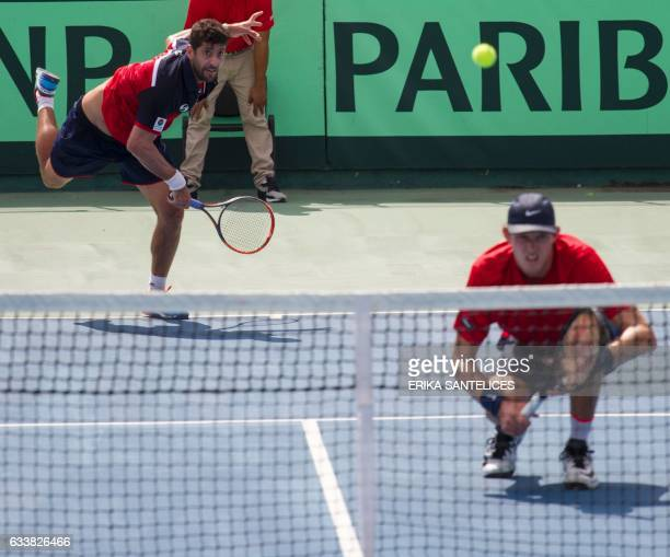 Hans Podlipnik of Chile returns the ball next to teammate Nicolas Jarry during the Davis Cup first round double tennis match against the Dominican...