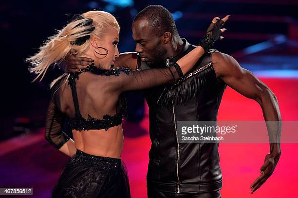 Hans Sarpei and Kathrin Menzinger perform on stage during the 3rd show of the television competition 'Let's Dance' on March 27 2015 in Cologne Germany