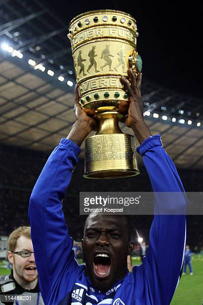 Hans Sarpei of Schalke lifts the trophy after winning 50 the DFB Cup final match between MSV Duisburg and FC Schalke 04 at Olympic Stadium on May 21...