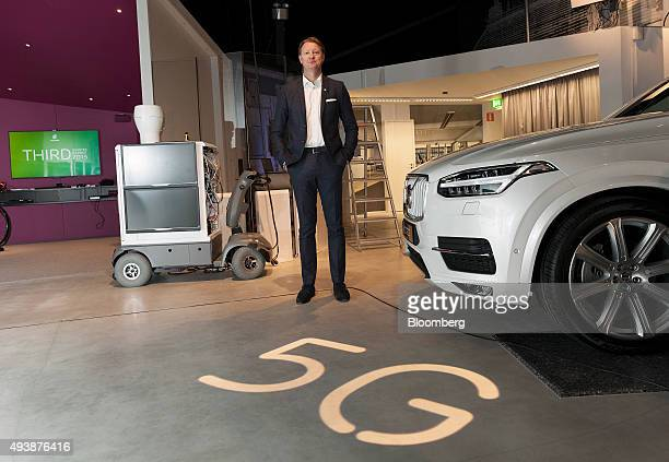 Hans Vestberg chief executive officer of Ericsson AB poses for a photograph beside a 5G base station prototype left and a Volvo Cars XC90 automobile...