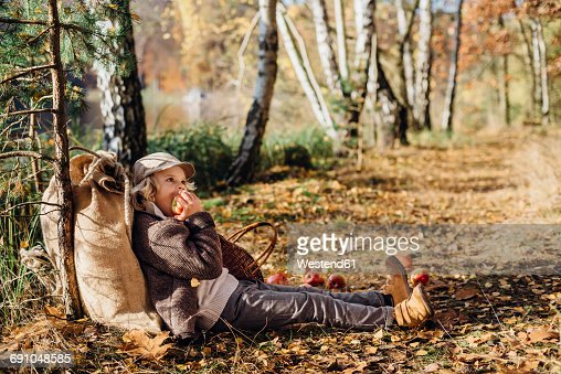 Hansel and Gretel, Boy leaning against tree in forest, eating apple