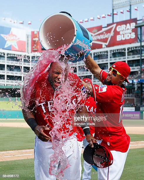 Hanser Alberto of the Texas Rangers left reacts to a sports drink shower from Rougned Odor in celebration of a 53 win over the Kansas City Royals in...