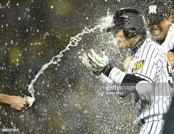 Hanshin Tigers' Fumihito Haraguchi is doused with water by his teammates on June 15 after hitting the gameending single in the 10th inning of an...