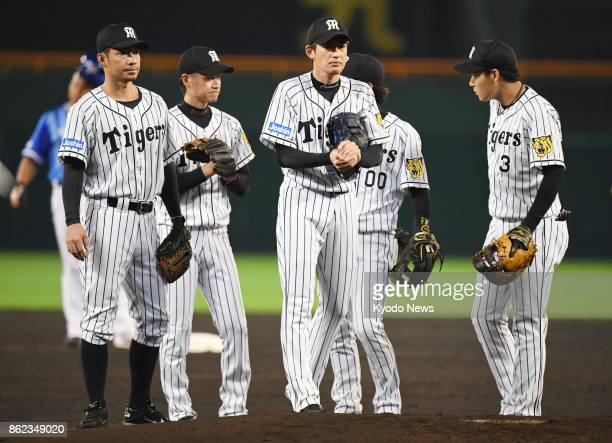 Hanshin Tigers infielders gather at the mound after starting pitcher Atsushi Nomi got in a jam in the first inning against the DeNA BayStars in Game...