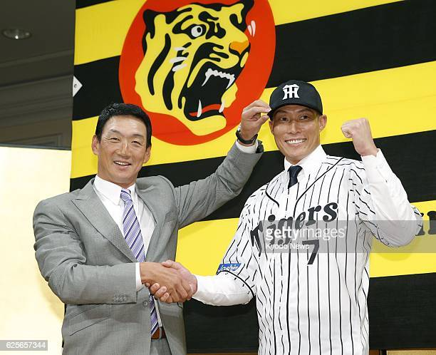 Hanshin Tigers manager Tomoaki Kanemoto and newly signed outfielder Yoshio Itoi shake hands at a press conference in Osaka on Nov 25 2016 Itoi was...