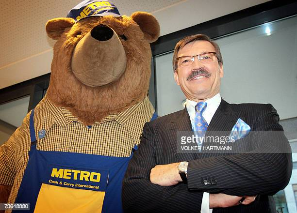 HansJoachim Koerber chairman of the German retail and distribution giant Metro poses beside his company's mascot prior to a press conference 21 March...