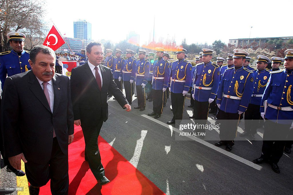 Hans-Peter Friedrich, German Federal Minister of the Interior, (3rdL) and his Turkish counterpart Muammer Guler (2ndL) review police honour guards before a meeting in Ankara, on February 7, 2013. AFP PHOTO/ADEM ALTAN