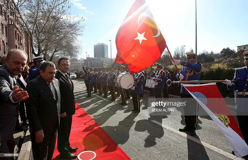 Hans-Peter Friedrich, German Federal Minister of the Interior, (3rdL) and his Turkish counterpart Muammer Guler (2ndL) review police honour guards before a meeting in Ankara, on February 7, 2013.