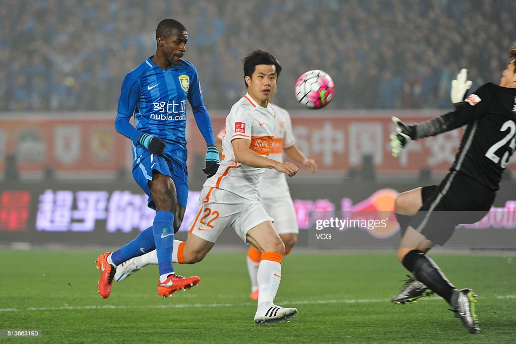 Hao Junmin of Shandong Luneng and Ramires of Jiangsu Suning compete for the ball during the first round match of CSL Chinese Football Association...