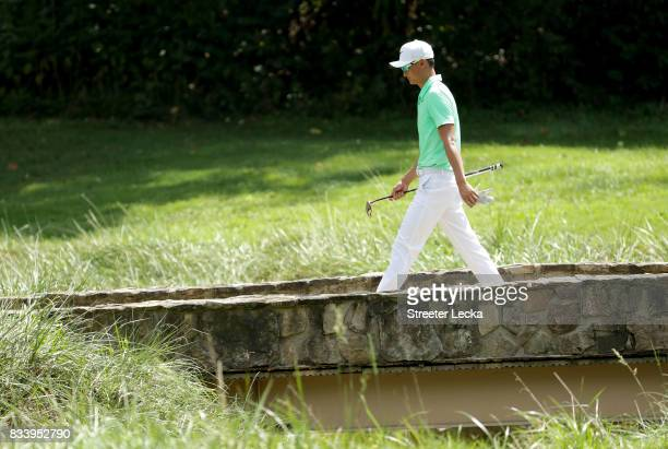 Hao Tong Li of China walks over a bridge on the sixth hole during the first round of the Wyndham Championship at Sedgefield Country Club on August 17...