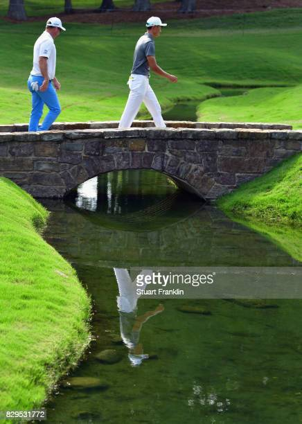 Haotong Li of China and Ryan Fox of New Zealand cross a brige during the first round of the 2017 PGA Championship at Quail Hollow Club on August 10...