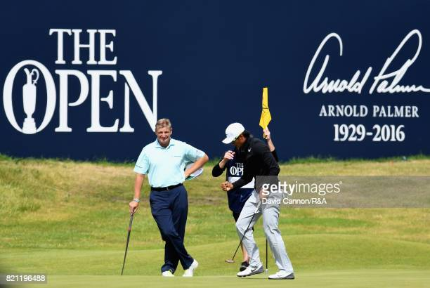 Haotong Li of China celebrates a birdie on the 18th green watched by Ernie Els of South Africa during the final round of the 146th Open Championship...