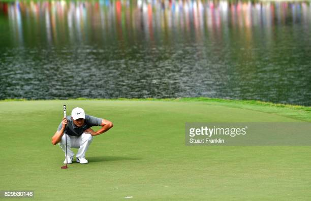 Haotong Li of China lines up a putt on the 17th green during the first round of the 2017 PGA Championship at Quail Hollow Club on August 10 2017 in...