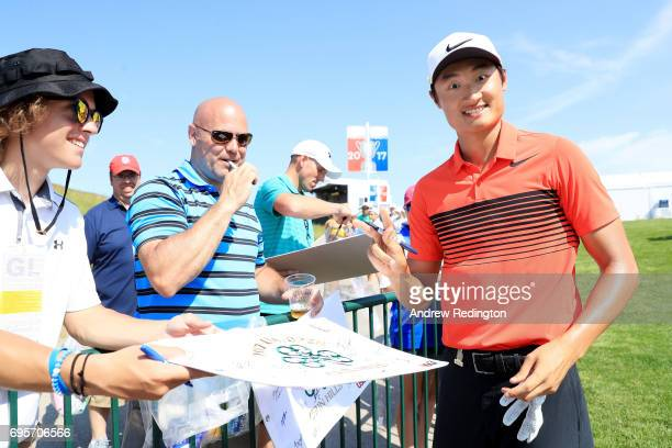 Haotong Li of China poses for a photo as he signs autographs during a practice round prior to the 2017 US Open at Erin Hills on June 13 2017 in...