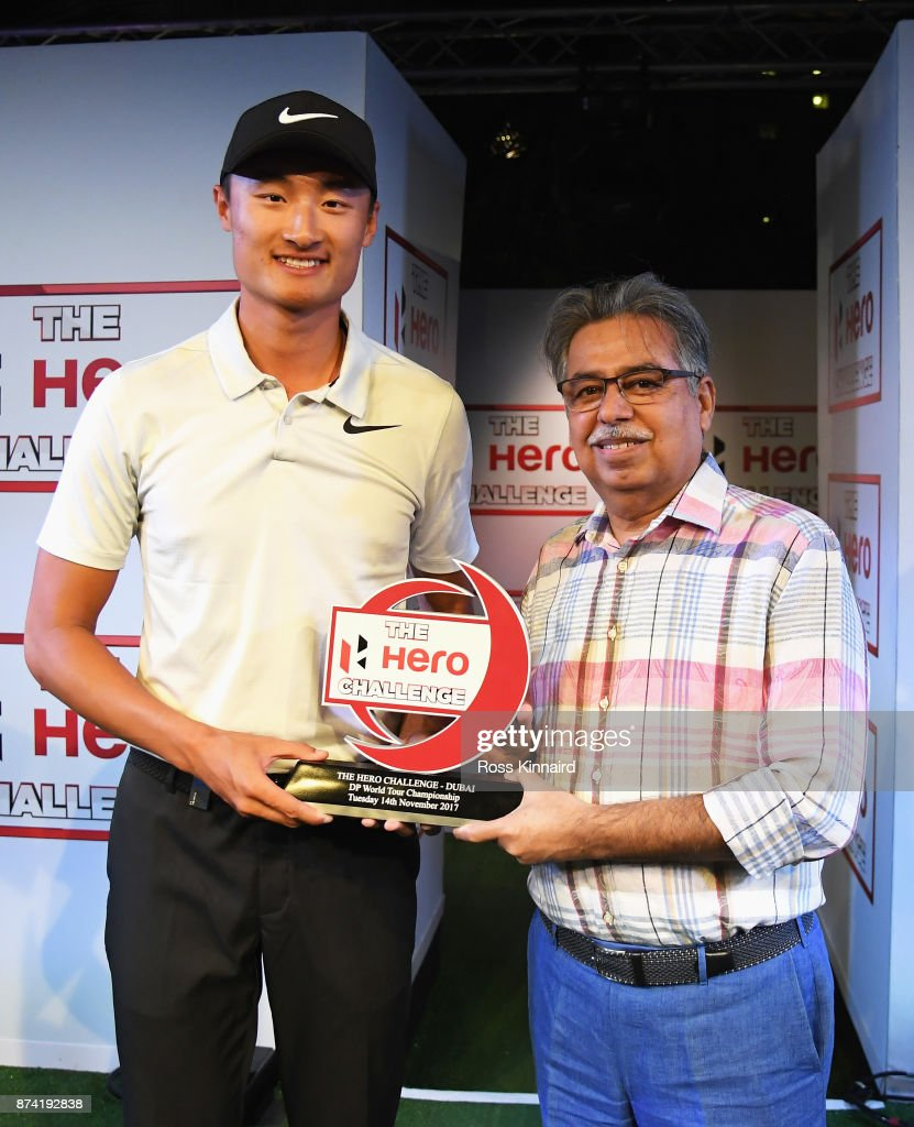 Haotong Li (L) of China receives the winners trophy from Pawan Munjal, Chairman, Managing Director and CEO of Hero MotoCorp after the Hero Challenge Final against Alex Noren of Sweden prior to the DP World Tour Championship at Atlantis, The Palm on November 14, 2017 in Dubai, United Arab Emirates.