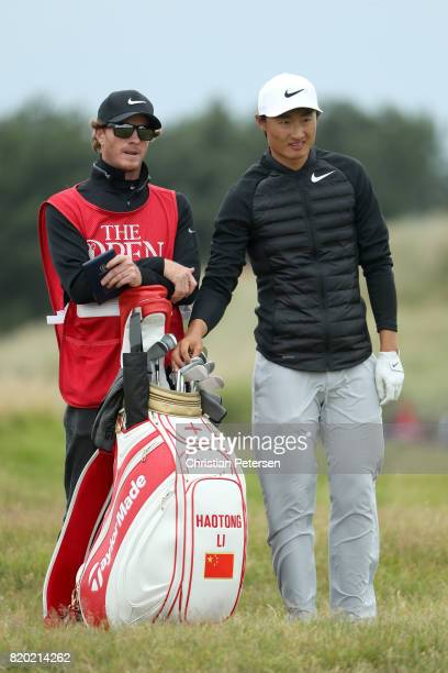 Haotong Li of China selects a club with his caddie during the second round of the 146th Open Championship at Royal Birkdale on July 21 2017 in...