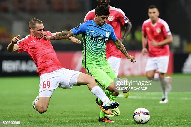 Hapoel Beer Sheva's Hungarian midfielder Mihaly Korhut vies for the ball with Inter Milan's Argentinan midfielder Ever Banega during the Europa...
