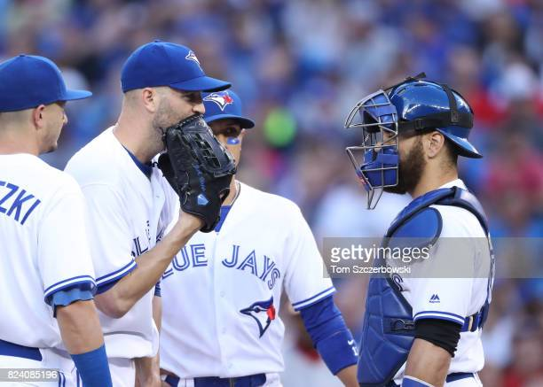A Happ of the Toronto Blue Jays checks with Russell Martin after not getting a favorable call on a basesloaded walk in the second inning during MLB...