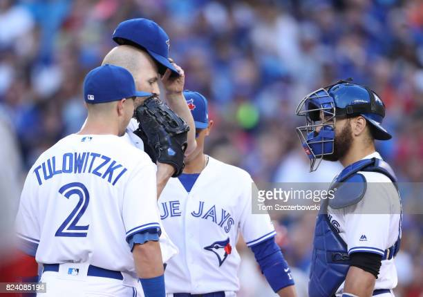 A Happ of the Toronto Blue Jays checks with Russell Martin as they meet on the mound after not getting a favorable call on a basesloaded walk in the...