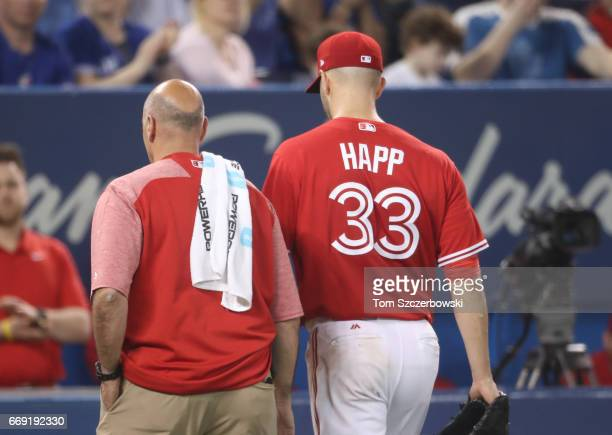 A Happ of the Toronto Blue Jays exits the game with trainer George Poulos due to an arm injury in the fifth inning during MLB game action against the...