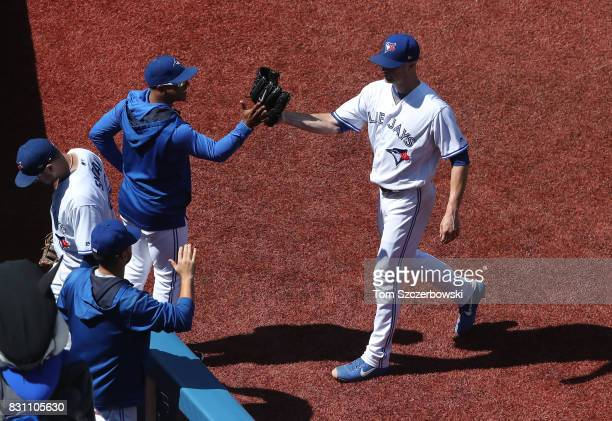 A Happ of the Toronto Blue Jays is congratulated by Marcus Stroman as he walks to his dugout after getting the last out of the sixth inning during...