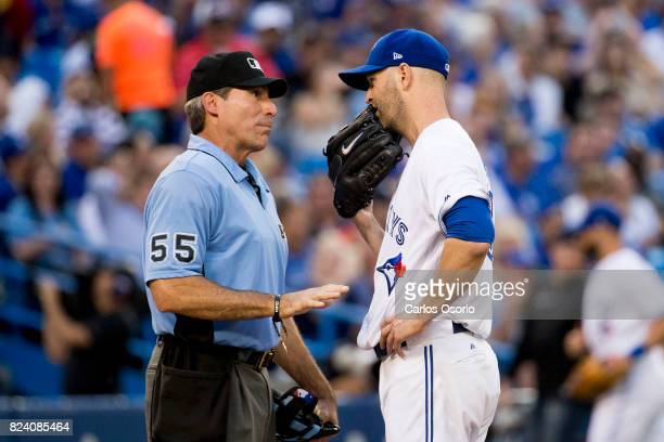 A Happ of the Toronto Blue Jays speaks with home plate umpire Angel Diaz after the 2nd inning of MLB action as the Toronto Blue Jays host the Los...