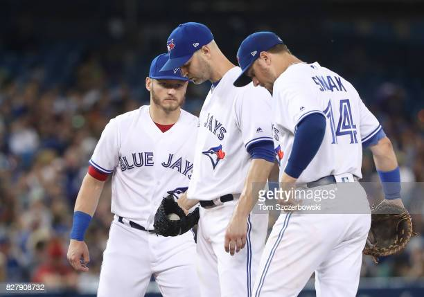 A Happ of the Toronto Blue Jays waits for manager John Gibbons moments before beig relieved as Josh Donaldson and Justin Smoak congratulate him in...