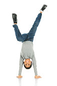 An elementary boy deslightedly standing on his hands.  On a white background.