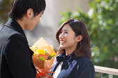 Happily smiling young female receiving a bouquet f