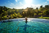 happiness concept. Woman sunbathing in infinity swimming pool at luxurious resort