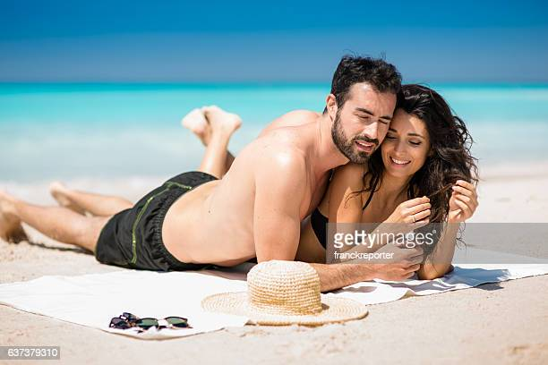 Happiness couple at the seaside lying down and laughing