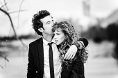 Cute couple embraces. black and white portrait of the stylish young man in a suit with a tie hugs the beautiful girl and kisses. The concept of a successful relationship and happy moments. Fashion wed