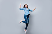 Happiness, freedom, power, motion and people concept - full length portrait of smiling young woman jumping  with raised fists over grey background