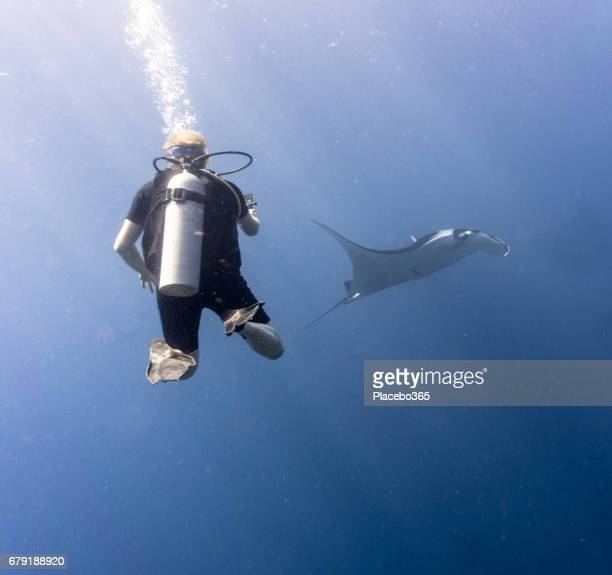 Happiness in Nature: Man enjoying nature scuba diving with and photographing an Endangered Species Pelagic Oceanic Manta Ray (Manta birostris). The location is Hin Muang Archipelago, Krabi, Andaman Sea, Thailand.