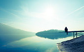 Woman sitting on the shore of the lake. Clear sunny day.