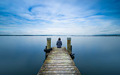 One woman sits on a wooden pier. Cloudy above the lake. Long exposure.