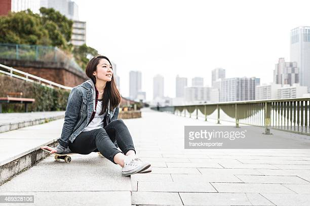 Bonheur Femme japonaise se détendre avec son skateboard