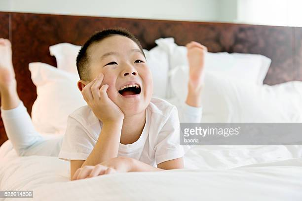 Happiness little boy lying in bed