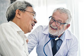 Happiness People.  Senior male Doctor and Asian male patient are talking in the medical room together. Smiling.