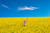 Outdoor shot of a happy girl in rapeseed field with arms raised up to blue sky