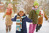 Happy girl holding her friends by hands in snowfall